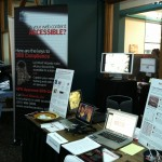 Our booth at IDEAS with poster about section 508 compliance and conference materials.